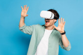 excited young man gesturing while using vr headset on blue