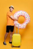 mladý vzrušený muž s kufrem a nafukovací koblihu připraven na letní dovolenou na žluté