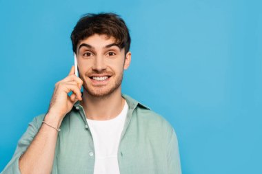 Happy young man talking on smartphone while looking at camera isolated on blue stock vector