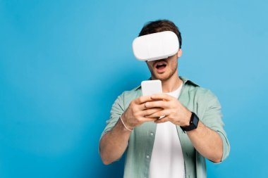 Shocked young man in vr headset using smartphone on blue stock vector