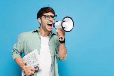 Aggressive man holding newspaper while screaming in megaphone on blue stock vector