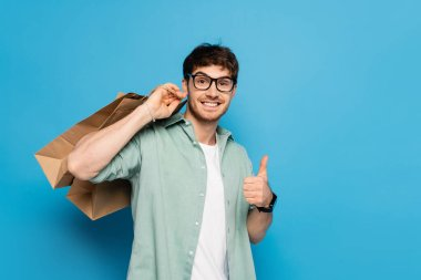 happy young man showing thumb up while carrying shopping bags on blue