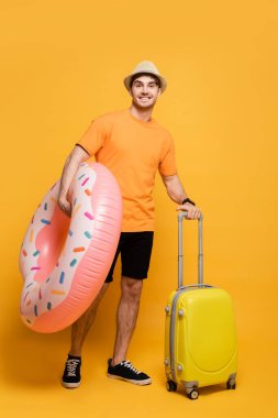 Smiling man with suitcase and inflatable donut ready for summer vacation on yellow stock vector