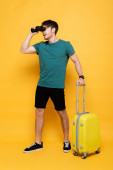 excited man with suitcase ready for summer vacation and looking through binoculars on yellow