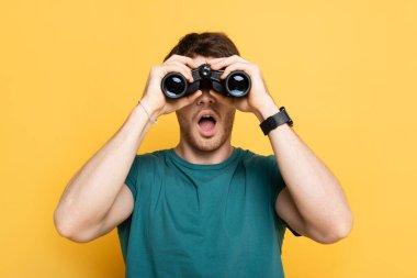 Young shocked man looking through binoculars on yellow stock vector