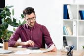 přemýšlivý podnikatel pomocí kalkulačky při prohlížení dokumentů na pracovišti
