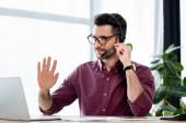 Lächelnder Geschäftsmann mit Kopfhörer winkt bei Videokonferenz auf Laptop