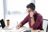 konzentrierter Geschäftsmann in Headset-Schrift auf Papier während einer Online-Konferenz am Laptop