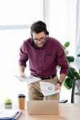 junger Geschäftsmann in Headset hält Dokumente während Videoanruf auf Laptop