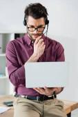 junger, seriöser Geschäftsmann im Headset mit Laptop im Videochat