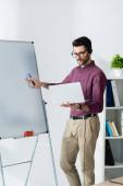 Konzentrierter Geschäftsmann hält Laptop in der Nähe von Flipchart