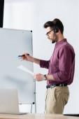 konzentriert Geschäftsmann in Headset-Schrift auf Flipchart, während Dokument in der Nähe Schreibtisch mit Laptop