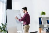 junger Geschäftsmann in Headset-Schrift auf Flipchart, während er Dokument in Schreibtischnähe mit Laptop hält