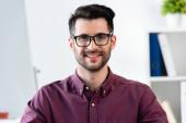 glücklicher, gutaussehender Geschäftsmann mit Brille, der in die Kamera lächelt