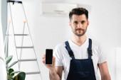 pohledný opravář ukazuje smartphone s prázdnou obrazovkou v blízkosti žebříku a klimatizace na stěně