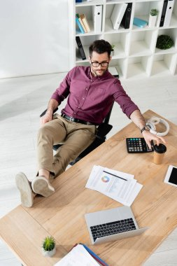 high angle view of young businessman sitting with legs on desk and taking coffee to go
