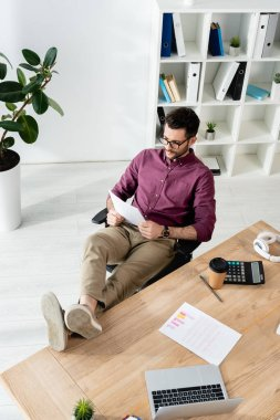 young businessman reading document while sitting with legs on desk near laptop, calculator and coffee to go