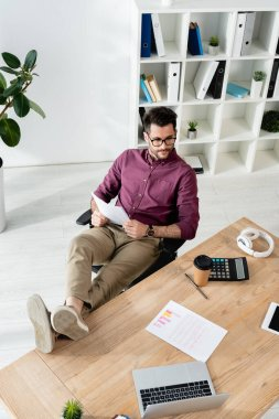 high angle view of businessman holding document while sitting with legs on desk near laptop, calculator and coffee to go
