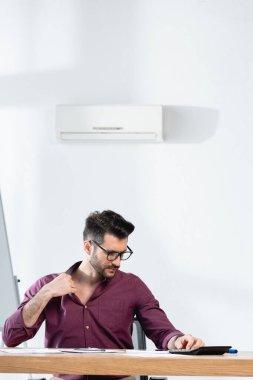 İş yerinde oturan genç işadamı ofiste sıcaktan acı çekerken gömleğine dokunuyor.