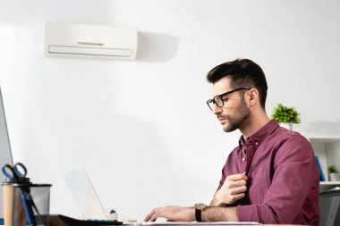 Young businessman touching shirt while working on laptop and suffering from heat near air conditioner stock vector