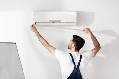 Young repairman measuring air conditioner fixed on white wall in office stock vector