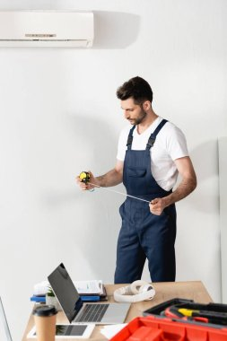 repairman holding measuring tape while standing near office desk under air conditioner