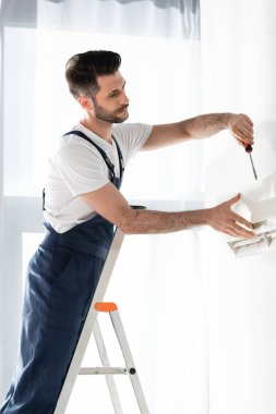 handsome repairman standing on stepladder and fixing air conditioner with screwdriver