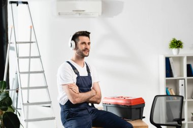 workman in wireless headphones sitting on desk with crossed arms near toolbox and air conditioner on wall