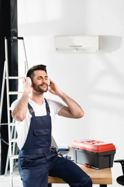 repairman with closed eyes sitting on desk in wireless headphones near toolbox and air conditioner on wall