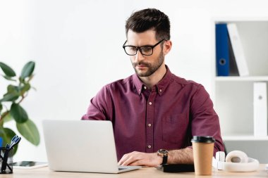 concentrated businessman typing on laptop in office