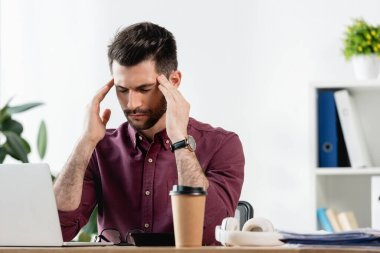exhausted businessman with closed eyes touching head while sitting near laptop and coffee to go