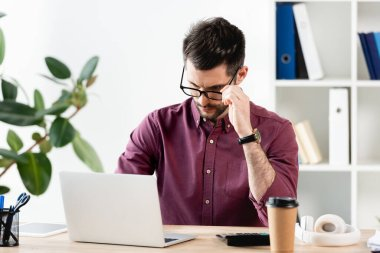 serious businessman touching glasses while sitting at workplace near laptop