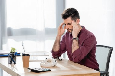 tired businessman touching head while suffering from migraine with closed eyes