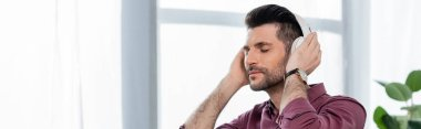 horizontal image of dreamy businessman listening music in wireless headphones in office