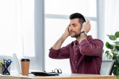 dreamy businessman with closed eyes touching wireless headphones while sitting at workplace near coffee to go