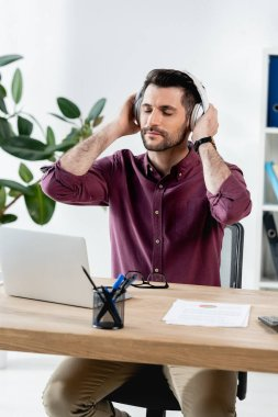 pensive businessman with closed eyes touching wireless headphones while sitting at workplace