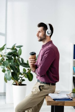 side view of thoughtful businessman in wireless headphones holding coffee to go while sitting on desk near potted plant