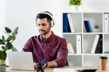 attentive businessman in wireless headphones working on laptop at workplace