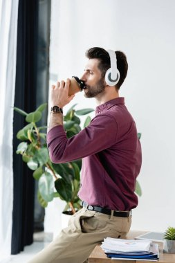 side view of businessman drinking coffee to go while sitting at desk