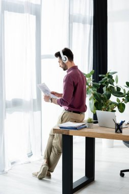 businessman in wireless headphones looking at document while sitting on desk near window