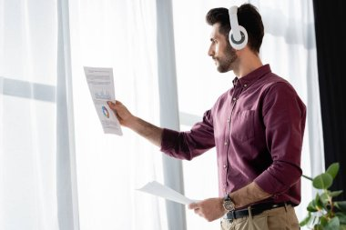businessman in wireless headphones looking at paper with business analytics near window