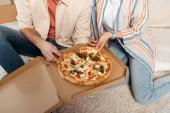 Oříznutý pohled na pár drží kousky pizzy v krabici na podlaze