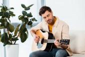 Hezký muž hraje na akustickou kytaru na gauči