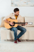 Young man performing on acoustic guitar on sofa in living room