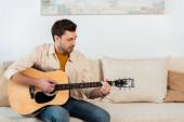 Hezký muž hraje na akustickou kytaru na pohovce v obývacím pokoji