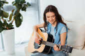 Beautiful smiling woman playing acoustic guitar in living room