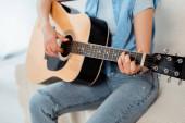 Oříznutý pohled mladé ženy vystupující na akustické kytary na pohovce