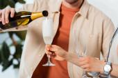 Oříznutý pohled na muže nalévání šampaňského, zatímco žena drží brýle