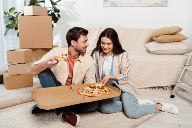 Smiling woman holding pizza near boyfriend and cardboard boxes on floor in living room stock vector