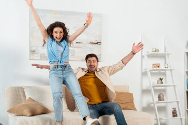 Cheerful couple with raised hands looking at camera in living room stock vector